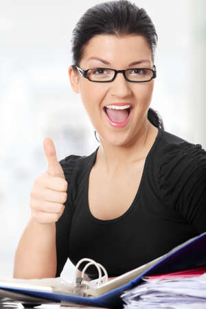Young woman at the desk gesturing OK  photo