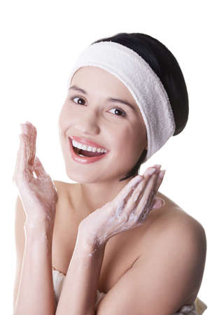 Beautiful happy woman is cleaning her face  photo