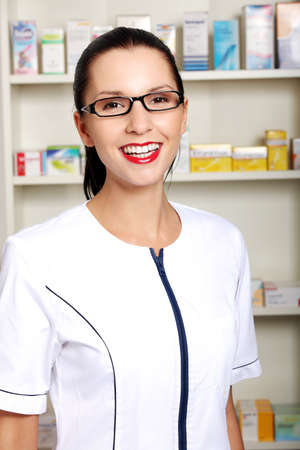 Young woman in pharmacist uniform standing in drugstore  photo