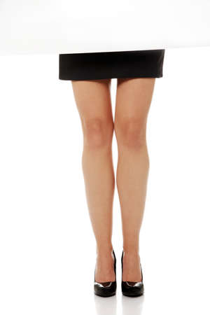 Beautiful slim businesswoman legs in elegant shoues and skirt behind blank board photo