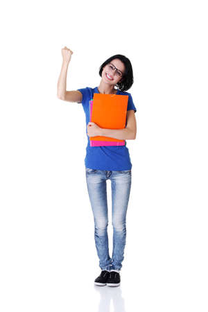 Happy student woman with notebooks showing win gesture with fist, isoalted on white background  photo