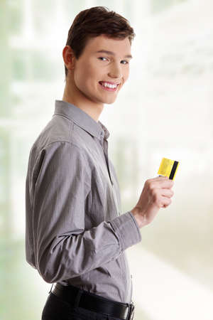 Young happy businessman holding credit card, isolated on white background Stock Photo - 16676135