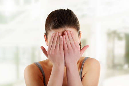 Scared woman hiding her face in hands Stock Photo - 16676099