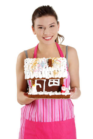 Young housewife woman in apron holding gingerbread house model, isolated on white background photo