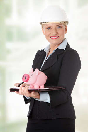 Mature engineer woman with piggybank.  photo
