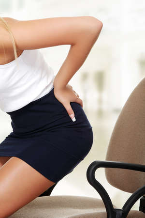 Business woman with back pain after long work on chair. Stock Photo - 15407277