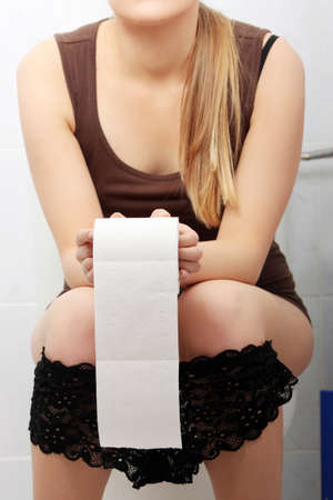 pee: Woman sitting on a toilet holding toilet paper. Stomach issues concept.