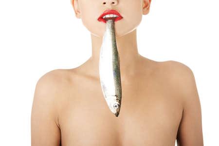 Красивая молодая женщина с рыбой в ее рот Фото со стока