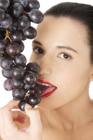 Beautiful sensual brunette eating grapes, isolated on white background  photo