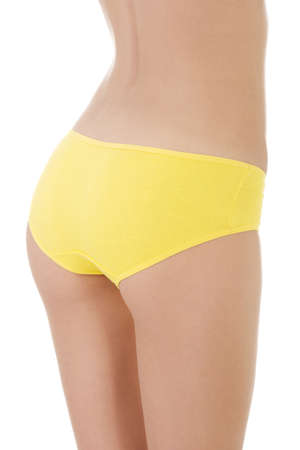 Slim tanned woman's body in yellow panties. Isolated over white background.  photo