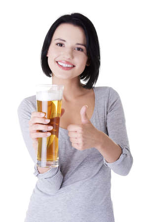 Beautiful and sexy young woman with glass of beer gesturing thumbs up, isolated on white  photo