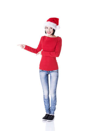 Beautiful smiling christmas santa woman pointing on side showing copyspace. Isolated on white background.  Stock Photo