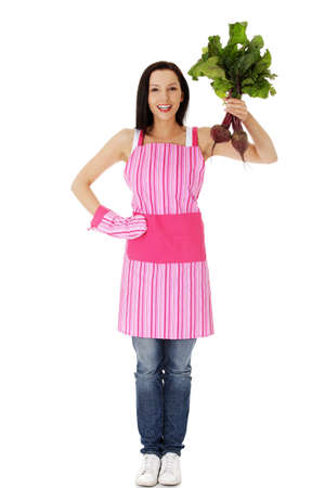 Happy woman in  pink kitchen appron holding beetroot    photo