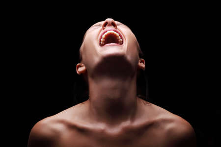 Screaming woman over black background Imagens