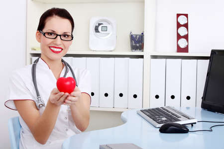 Pretty caucasian female doctor in uniform holding red heart.  photo
