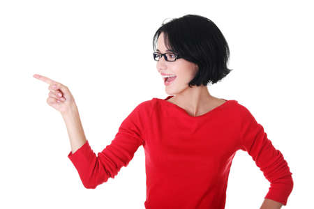 Happy , excited young woman pointing on copy space, isolated on white  版權商用圖片