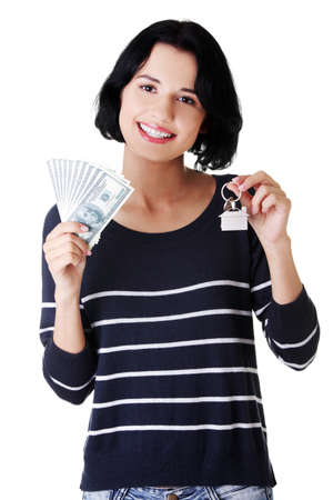 Beautiful young woman holding US dollars bills and house model over white - real estate loan concept  photo