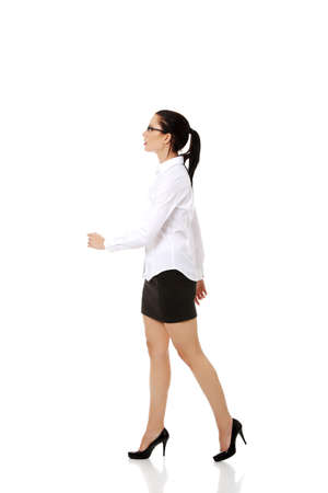 Side view of walking elegant businesswoman photo