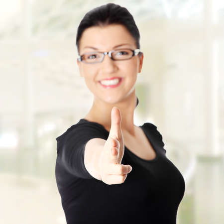 Young beautiful happy caucasian woman pointing on you . Focus on hand photo