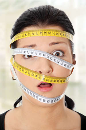 Beautiful young caucasian woman with measuring tape around her hea. Diet concept