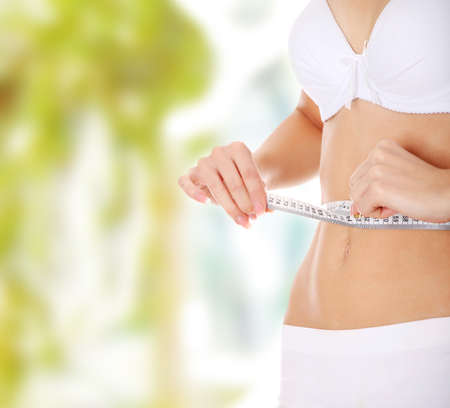 lose weight: Beautiful woman measuring her perfect shape of beautiful thigh waist. Healthy lifestyles concept .  Stock Photo
