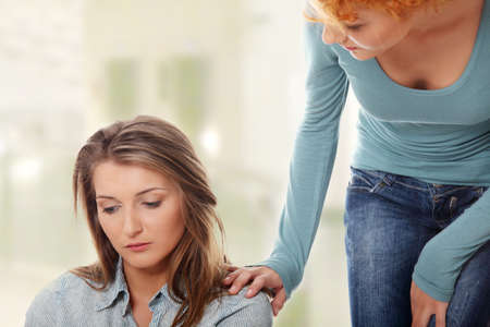 emotional woman: Troubled young girl comforted by her friend.
