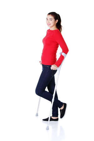 Woman walking with crutches becouse of leg injury  Isolated on white  photo