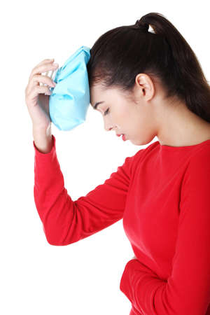 Woman with ice bag for headaches and migraines , isolated on white  photo