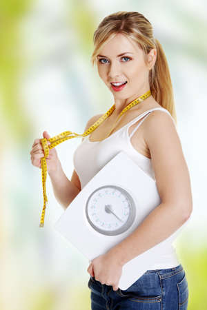 Woman with bathroom scale and measuring tape photo