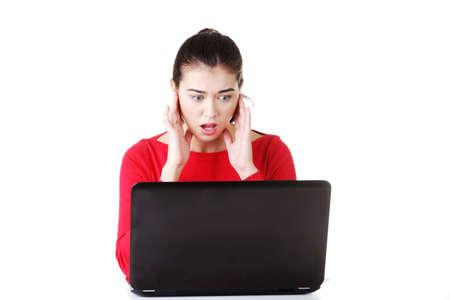 pornografia: Casual mujer joven delante de la computadora port�til aislado en blanco Foto de archivo