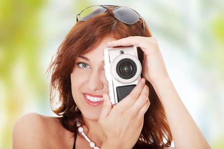 Young beautiful smiling woman holding a micro four thirds photo camera. photo