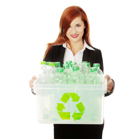 Young businesswoman carrying a plastic container full with empty recyclable household material. Recycling concept  photo