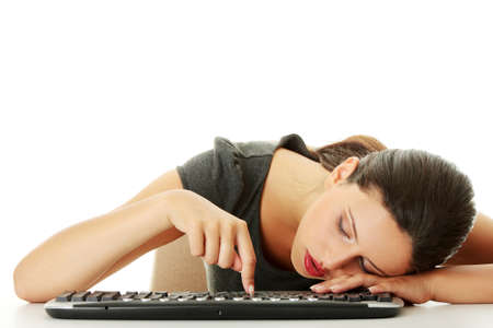 Tired businesswoman typing on keyboard, isolated on white photo