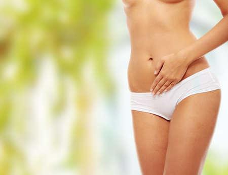 dolor de estomago: Hermoso cuerpo femenino aislados en blanco. Sexy joven en bragas blancas