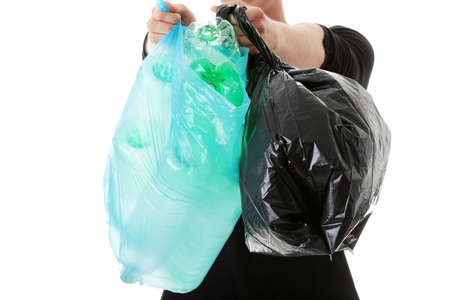 dispose: Close up on teen man carrying a plastic trash bags full with empty recyclable household material.  Stock Photo