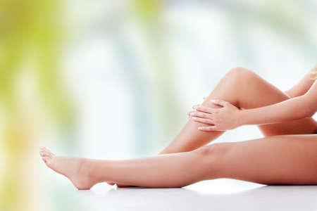 Mujer que sostiene en la pierna. Foto de archivo