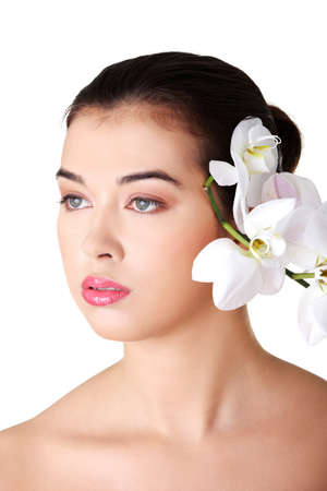 Portrait of beautiful young woman with health skin and with orchid flower  photo