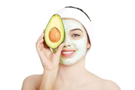 avocado: Mujer joven con una sonrisa la celebraci�n de aguacate m�scara de arcilla agitado cara en la cara en un spa Foto de archivo