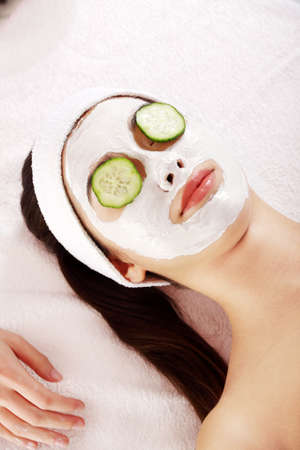 Young woman with cucumber slices on the face in a spa saloon photo