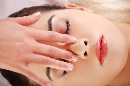 Красивая молодая расслабленной женщина нравится получать массаж лица в спа-салоне Фото со стока