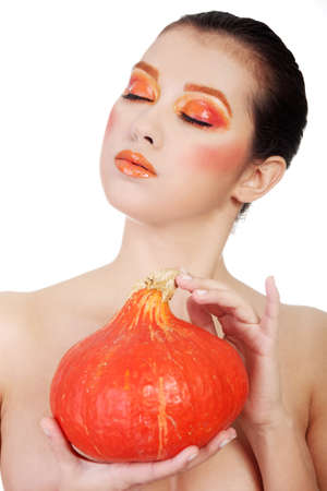 Beautiful woman with orange make up holding pumpkin photo