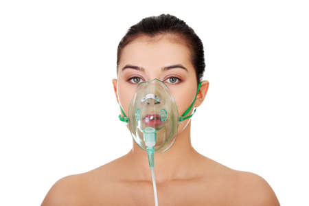 inhalation: Diseased female patient wearing a oxygen mask against white background
