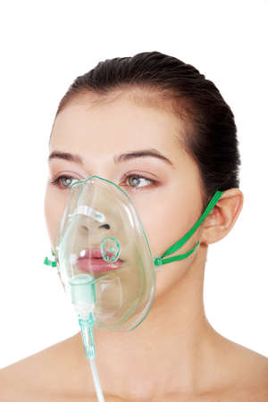 surgical mask woman: Diseased female patient wearing a oxygen mask against white background