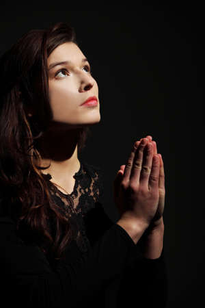 Closeup portrait of a young caucasian woman praying photo