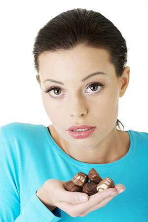 Young beautiful woman in casual clothes with hand full of chocolates Stock Photo - 16738854