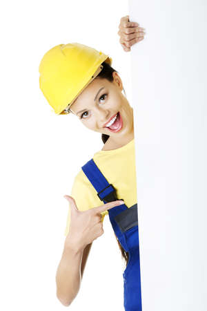 Female construction worker with blank board, isolated on white 版權商用圖片