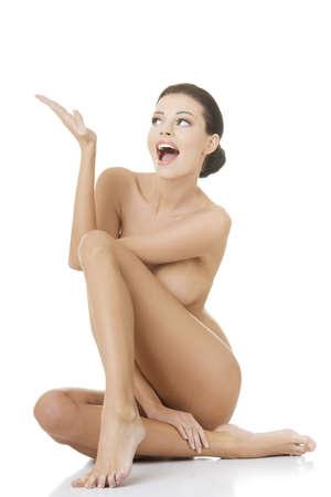 femmes nues sexy: Sexy femme nue avec ajustement sain peau propre montrant sur l'espace de copie, isol� sur fond blanc