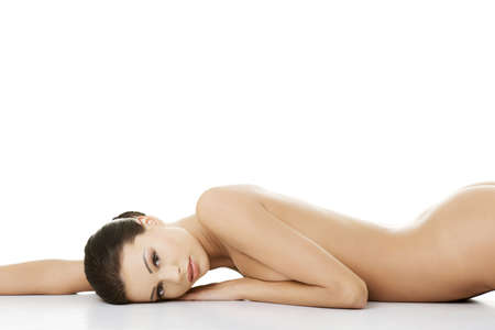 Beautiful happy  nude woman with fresh clean skin lying on belly