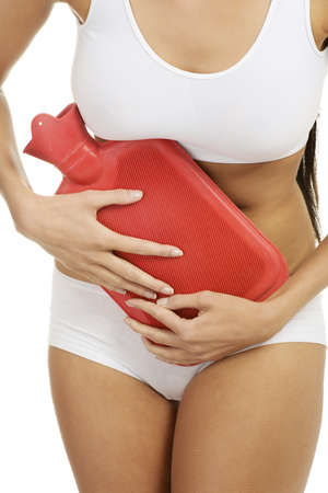 Close up of woman belly with hot water bottle photo