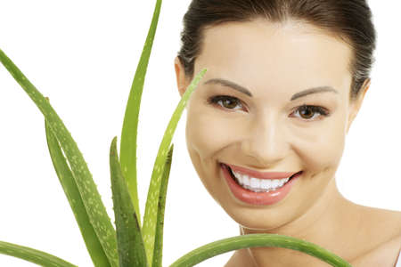 Young beautiful womans face and aloe vera. Isolated on white background  photo